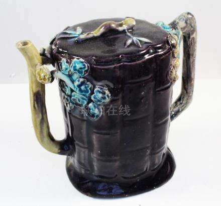 A 19th century Chinese Fahua Cadogan teapot decorated with flowers on an aubergine ground, 13cms (