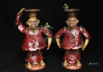 A pair of Chinese Shiwan glaze candlesticks in the form of clothed monkeys with four-character