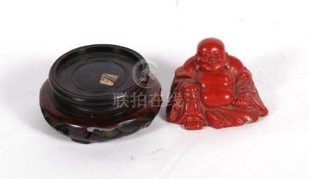 An early 20th century Chinese cinnabar lacquer figure of a seated Buddha, 5cms (2ins) high; together