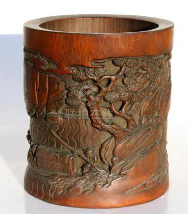A Chinese bamboo brush pot, deeply carved with boats and figures on a shoreline and calligraphy,