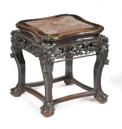 A late 19th century Chinese hardwood low stand, the top inset with a marble panel, above a carved