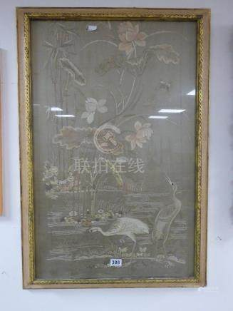 A 20TH CENTURY ORIENTAL SILK WORK OF CRANES BY FOLIAGE FRAMED AND GLAZED 97CM BY 65CM