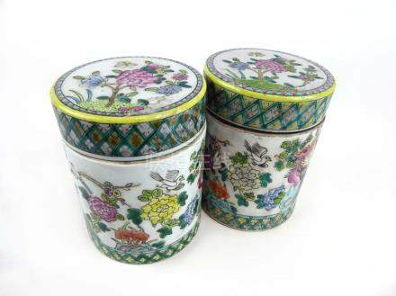 A pair of Cantonese jars and covers of cylindrical form decorated with exotic birds amongst
