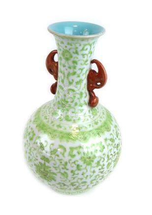 A Chinese two handled vase of elongated globular form decorated in pale green enamel with