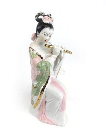 A porcelain figure modelled as a seated female playing the flute in the Chinese manner, h. 24.