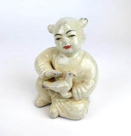 A Chinese glazed terracotta figure modelled as a seated child holding a bird, h. 14.
