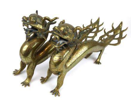 A pair of early 20th century Chinese cast brass figures, each modelled as an outstretched dragon, l.