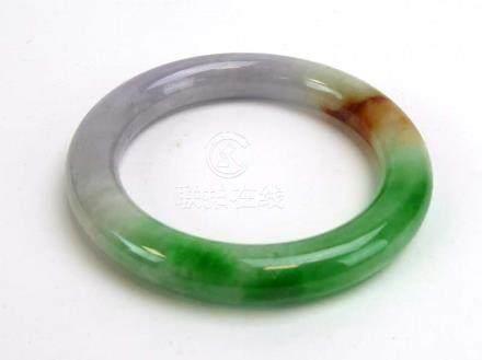 A pale green/brown jade bangle, internal d. 5.