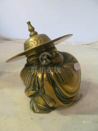A 19th Century brass oriental figure man crouching under a large hat