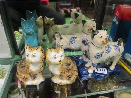 A pair of blue and white oriental style cats and three other cat ornaments.