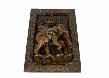 A 20th Century Indian carved wooden relief sculpture of three figures riding on an elephant, in a