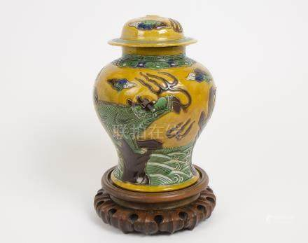 A large Chinese ginger jar and cover, decorated with temple dogs on a yellow background, character