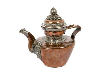 A late 19th Century Tibetan copper and silver teapot, domed cover with lotus bud final, applied