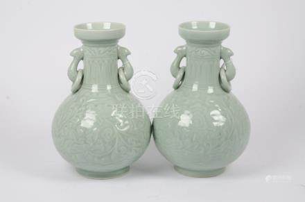 A pair of Chinese celadon glazed lamp bases, loop and ring handles, low relief foliate decoration,