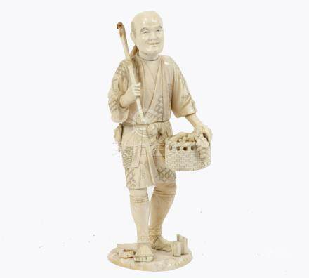 A Meiji period carved ivory figure of a farmer holding a scythe and basket of fruit and
