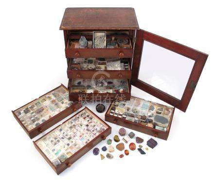 A wooden specimen cabinet, containing a variety of cased gemstones, including a large rough ruby and