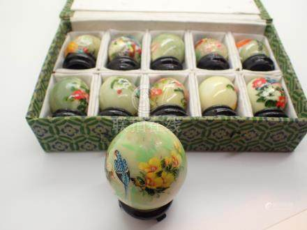 Cased set of ten Oriental hand painted jade eggs on ebonised wooden stands and one other