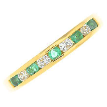 An 18ct gold emerald and diamond half eternity ring.