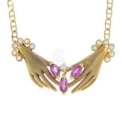 A ruby and diamond hand necklace.