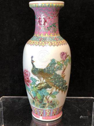 A Chinese porcelain famille rose decorated baluster vase, decorated with a peacock in a peony