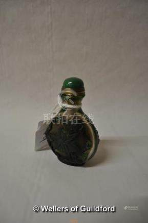 A Chinese glass snuff bottle, green cabochon stone to lid, carved with bats and leaves, 7cm.