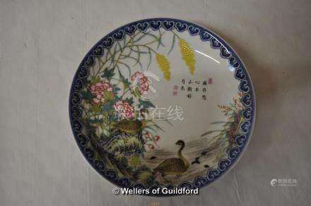 A Chinese polychrome plate decorated with a scene of geese amidst flowers and flowers, inscribed and