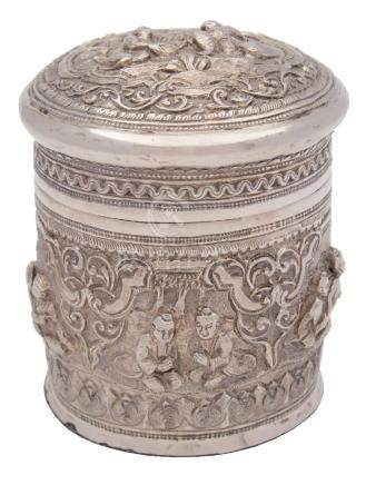 A Burmese silver jar and cover: the domed pull-off lid with embossed decoration of figures seated