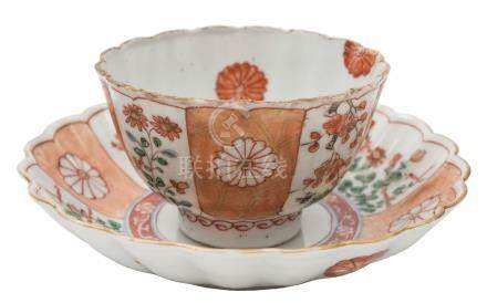 A Chinese famille verte fluted teabowl and saucer: painted with alternating panels of flowers and