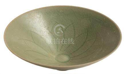A Chinese celadon bowl: of flared conical form, the interior carved with a stylised lotus flower,