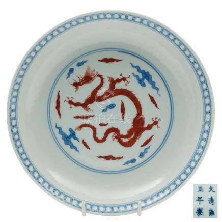 A Chinese underglaze blue and iron-red dragon dish: the interior medallion decorated with a sinuous