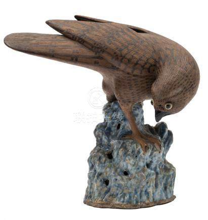 A Chinese stoneware model of a hawk: with brown biscuit plumage and dark markings,