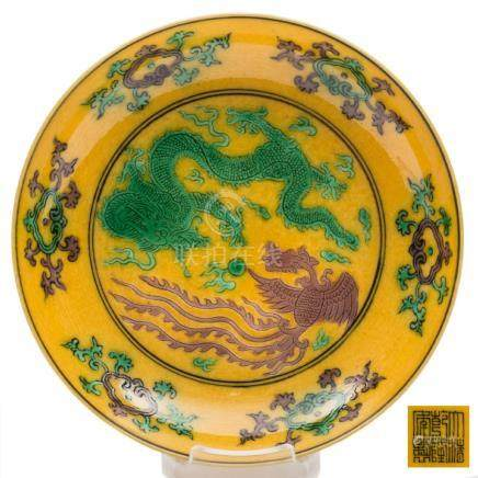 A small Chinese yellow ground phoenix and dragon dish: incised and painted in green and aubergine