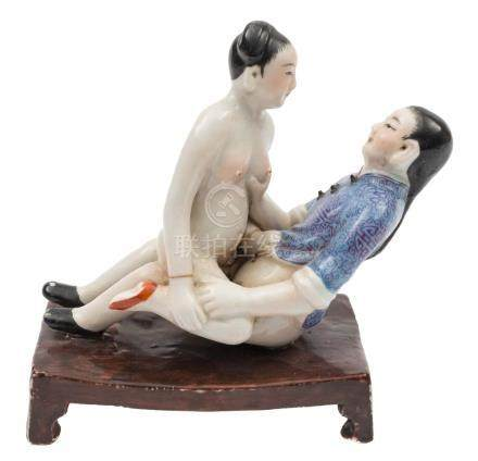 A Chinese porcelain erotic figural group: depicting an amorous man and woman,