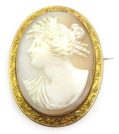 Cameo brooch in scrolled 9ct gold surround stamped 9ct