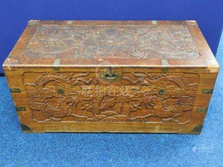 A Chinese carved camphor wood chest with brass fit
