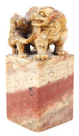 A 19thC Chinese soapstone desk ornament, profusely carved with two dragons, on a square base, in