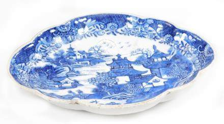 An 18thC Chinese export scalloped side dish, decorated with pagodas and two men on a bridge in