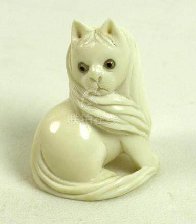A Japanese ivory netsuke, circa 1900, carved as a cat sitting looking over it's right shoulder,