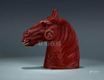 A carved cinnabar head of horse ornament