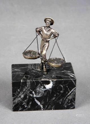 Figura de cenachero, en plata de ley, sobre peana de mármol.