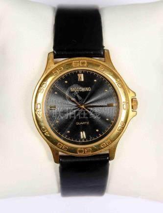 Reloj tipo MOSCHINO, en dorado con esfera en negro, aplicaci