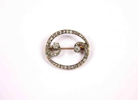 Broche oval decorado con dos brillantes y orla de brillantes