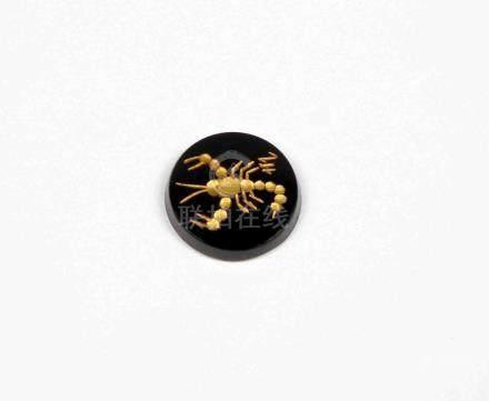 Ónix circular decorado con signo de Escorpio en oro.