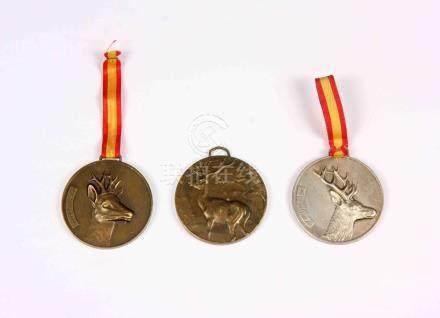 Lote formado por tres medallas, dos en bronce y una en plate