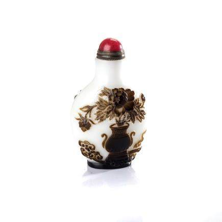 A CHINESE CARVED BROWN GLASS OVERLAY 'PEONY' SNUFF BOTTLE the compressed globular body raised on a
