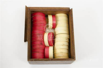 A set of 19th Century Cantonese ivory gaming counters, white and red-stained, each double carved
