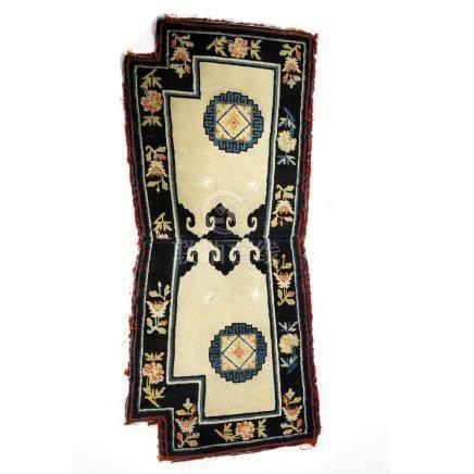 Chinese saddle rug ivory ground with black foliate banded border, 136cm x 59cm