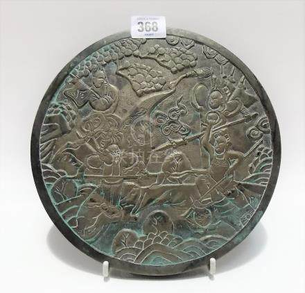 Chinese bronze circular plaque relief decorated with three warriors amongst foliage, diameter 21cm