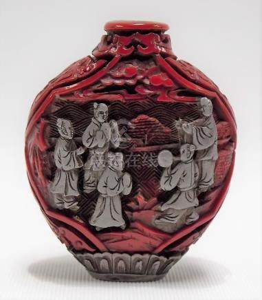 A white metal and cinnabar lacquer carved snuff bottle in the form of flattened baluster form
