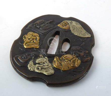 A Japanese brown patinated bronze tsuba relief decorated with theatrical masks, signed, l.